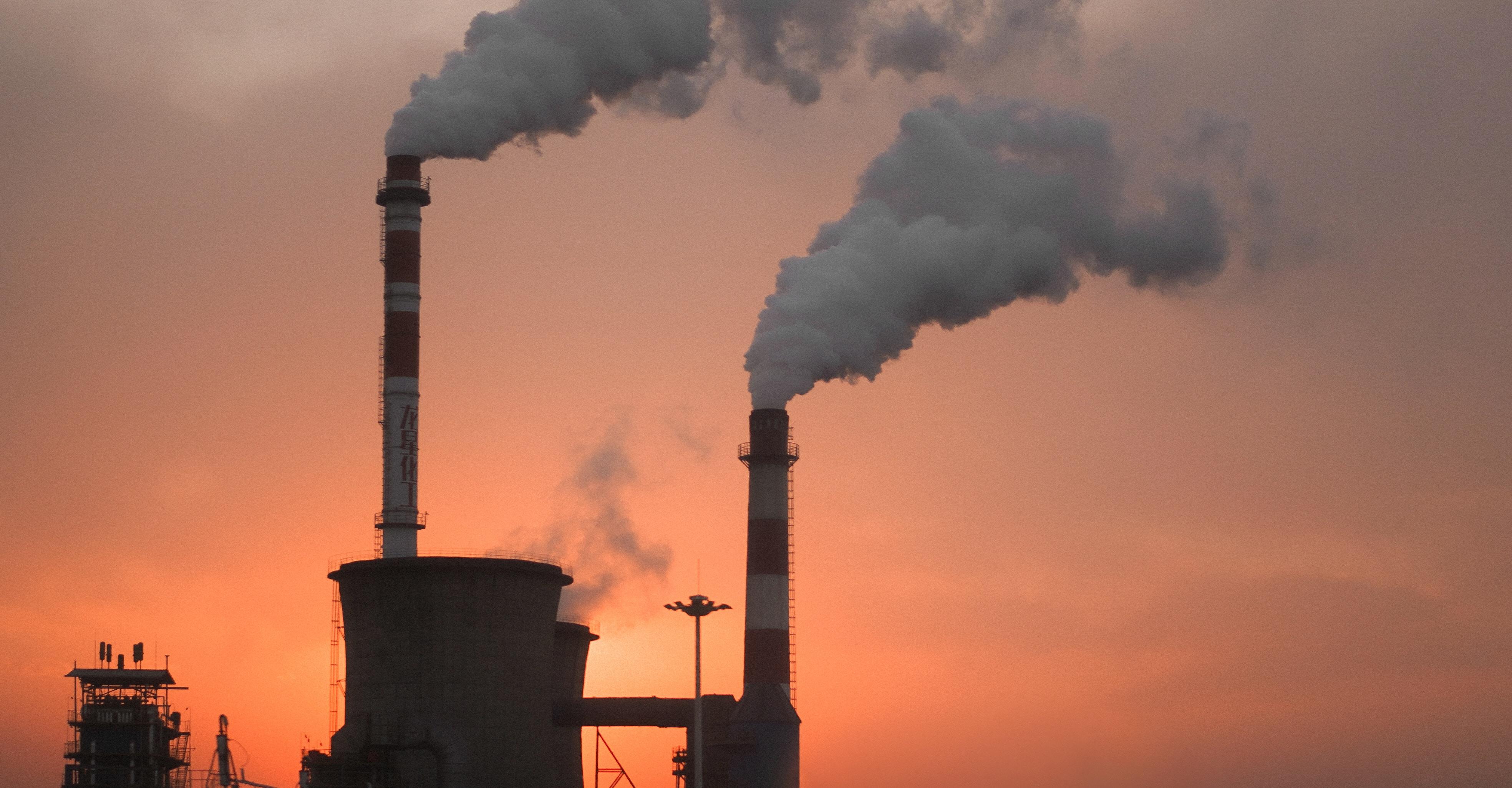 smoke leaving industrial chimneys at sunrise